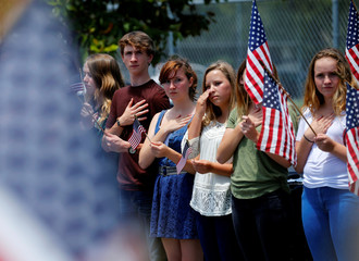 Students line the road as a funeral procession to Fort Rosecrans National Cemetery for U.S. Navy SEAL Charles H. Keating IV is held following a private service in Coronado