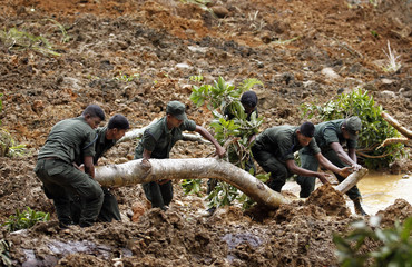 Members of a military rescue team search at the site of a landslide at the Koslanda tea plantation near Haldummulla