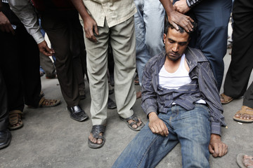 Investors stand near a man who fainted during a protest in front of the Dhaka stock exchange in Dhaka
