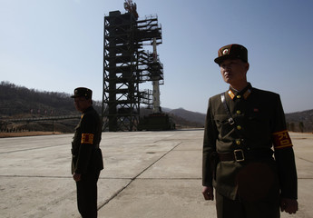 Soldiers stand guard in front of the Unha-3 (Milky Way 3) rocket sitting on a launch pad at the West Sea Satellite Launch Site, during a guided media tour by North Korean authorities in the northwest of Pyongyang