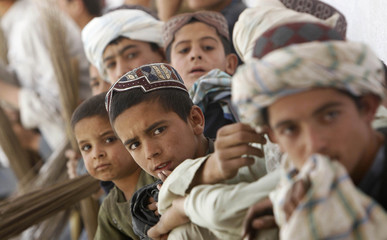 Afghani boys wait to be paid after cleaning an abandoned school at the village of Khwaja Mulk