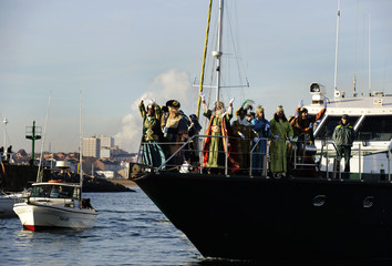 Men dressed as the Three Wise Men greet the crowd as they arrive by boat to the port of Gijon