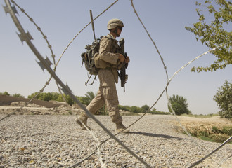 U.S. Marine of the Weapons Company, 1st Battalion, 3rd Marines, walks during a joint patrol with Afghan National Army soldiers near the Patrol Base Karma in Helmand province