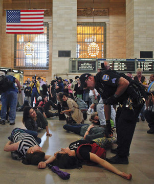 A policeman requests for Occupy Wall Street movement activists, who were lying on the floor of Grand Central Terminal in protest, to take their demonstration out onto the streets of New York