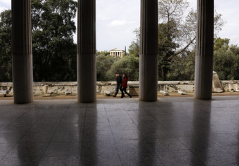 The temple of the ancient Greek god of Hephaestus (background) is seen as tourists walk by the Attalos arcade in Athens