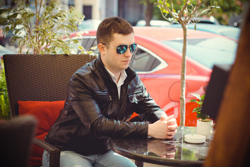 Lifestyle young man student in blue sunglasses walk around European streets