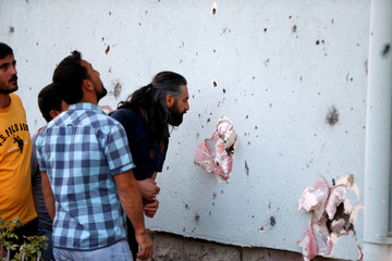 Men look at damage caused by fighting during a coup attempt at Turkish police special forces base near Ankara,Turkey