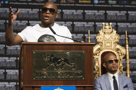 Floyd Mayweather Jr. speaks as Miguel Cotto sits in the background during a news conference at the MGM Grand Hotel and Casino in Las Vegas