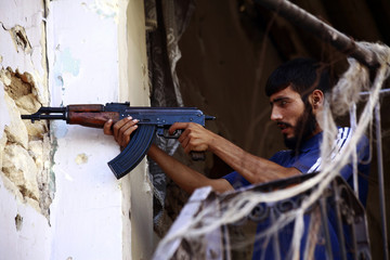 A Free Syrian Army fighter takes up a shooting position in Ogiwl