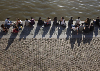 People rest by the Vltava river bank during a sunny evening in Prague