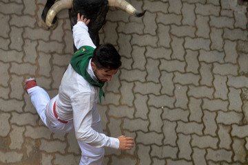 A runner sprints in front of a Jose Escolar Gil fighting bull near the entrance to the bullring during the third running of the bulls at the San Fermin festival in Pamplona