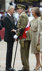 Spanish King Juan Carlos and Queen Sofia talk with Spain's Defence Minister Pedro Morenes at the end of a military parade in Valladolid