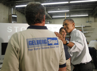 U.S. President Obama speaks with a worker during his visit to Gelberg Signs in Washington