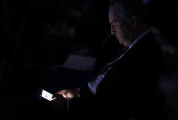 A participant uses his mobile device during as session of  World Economic Forum in Davos