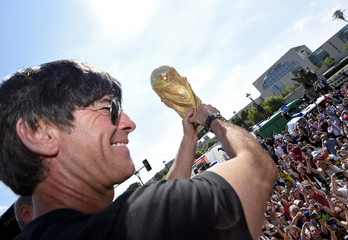 German national soccer team coach Loew displays the World Cup trophy to supporters during celebrations in Berlin