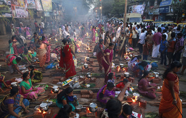 Devotees prepare ritual rice dishes to offer to the Hindu Sun God as they attend Pongal celebrations at a slum in Mumbai