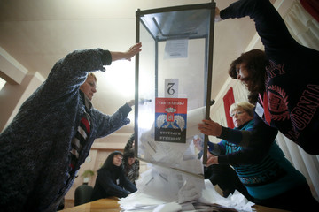 Members of a local electoral commission empty a ballot box at a polling station after voting day in Donetsk