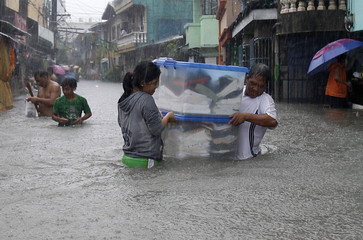 Residents carry their belongings as they wade through floodwaters brought by the monsoon rain, intensified by tropical storm Trami, in Paranaque city