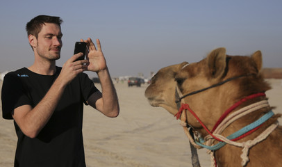 Goalkeeper Lichtlein of Germany takes pictures of a camel during a desert trip with his team during the men's Handball World Championship 2015, outside Doha