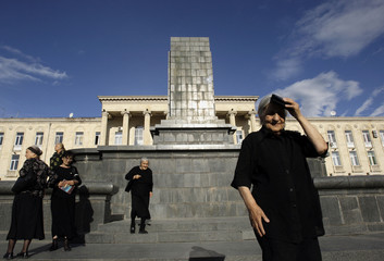 Women stand next to the empty pedestal of dismantled statue of Soviet dictator Josef Stalin at his hometown of Gori