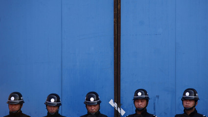 Policemen stand guard during a campaign to destroy pornographic and pirated publications in Beijing