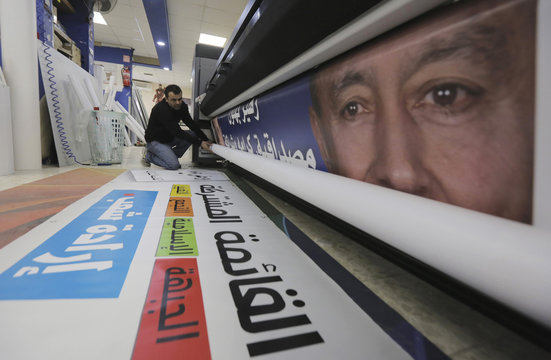 A worker kneels beside a freshly printed campaign poster for the Joint Arab List, at a print shop in the Arab Israeli town of Baqa al-Gharbiya