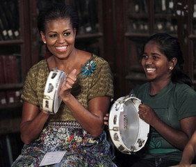 """U.S. first lady Michelle Obama plays a tambourine with underprivileged children enrolled in the academic program of """"Make A Difference"""" at a university in Mumbai"""