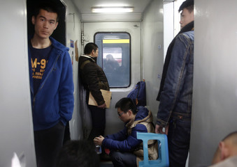 Passengers who have standing seat tickets stand in a train before leaving for Inner Mongolia at Beijing Railway Station during the travel rush ahead of the upcoming Spring Festival in Beijing