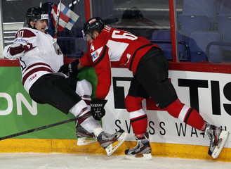 Austria's Lakos collides with Latvia's Darzins during their 2013 IIHF Ice Hockey World Championship preliminary round match at the Hartwall Arena in Helsinki