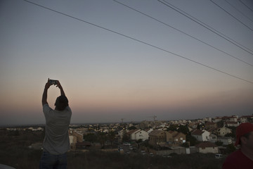 An Israeli teen takes a selfie, with the Gaza Strip on his background, on a hill near Sderot, opposite the northern Gaza Strip