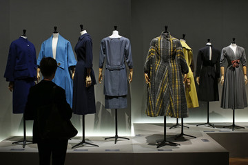"""A visitor looks at vintage dresses presented in the exhibition """"Les Annees 50, La mode en France"""" at the Palais Galliera  fashion museum in Paris"""
