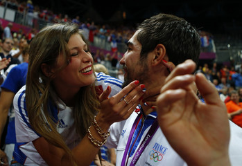 An unidentified woman smiles after kissing France's Nikola Karabatic at the men's handball victory ceremony during the London 2012 Olympic Games at the Basketball Arena