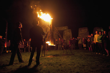 Compagnie Carabosse members light a metal structure as World Heritage site Stonehenge is illuminated during an elemental Fire Garden display, which is part of the London 2012 Festival, in Salisbury