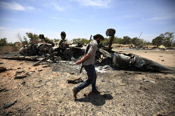A rebel fighter walks past a destroyed fighter jet during a patrol at Misrata's airport