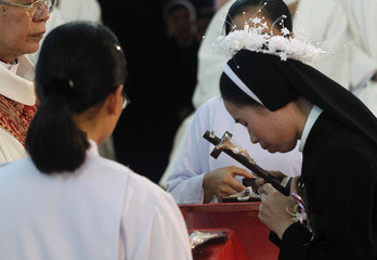 A Catholic nun kisses a Holy Cross as she attends a profession mass for the sisters of the congregation of Holy Cross's Lovers of Hung Hoa diocese in Son Tay town