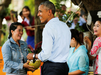U.S. President Obama laughs along with women who accidentally sprayed him with fresh coconut water as they were cutting into a coconut for him on a walk in Luang Prabang