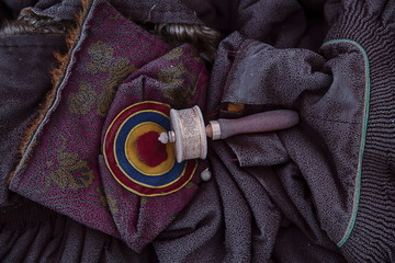 Frost remains on a prayer wheel, traditional Tibetan hat and monks robes as people gather in sub zero temperature at Buddhist laymen lodge for morning chanting session during the Utmost Bliss Dharma Assembly in remote Sertar county