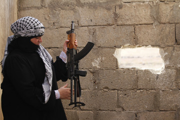 Bushra Kaake holds her weapon next to the Syrian government's air intelligence center in Aleppo