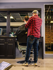 Adult male barber and customer in shop