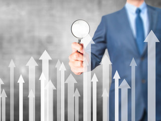 Sales Growth Graph - Business man holding magnifying glass on screen interface