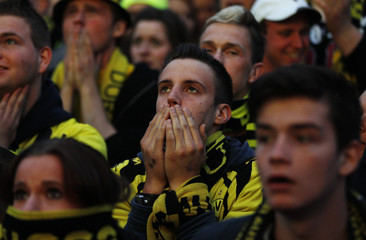 Borussia Dortmund soccer fans react at a public viewing event in Dortmund