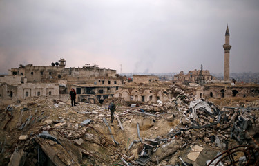 A member of forces loyal to Syria's President Bashar al-Assad stands with a civilian on the rubble of the Carlton Hotel, in the government controlled area of Aleppo