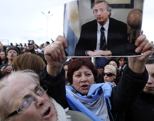 A woman holds up a picture of former Argentine President Nestor Kirchner as she watches the hearse carrying his remains arrive at his hometown of Rio Gallegos