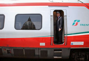 A Trenitalia's conductor looks as the St. Peter Dome is reflected on a window of a Frecciargento's train at the Vatican railway station in Vatican