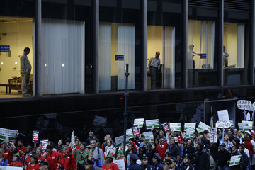Bankers from Bank of India watch from a window as Occupy Wall Street protesters march 47th Street in New York