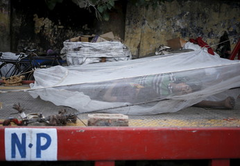 Workers sleep under a mosquito net installed on an open truck on a hot summer day in New Delhi