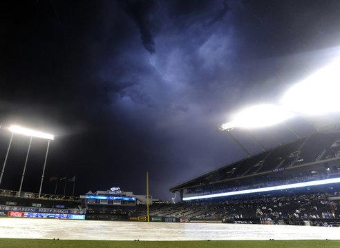 Lightning illuminates the sky over Kauffman Stadium during a rain delay during the Yankees Royals MLB baseball game in Kansas City