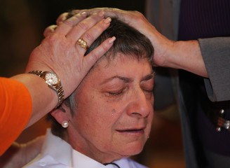 Rosemarie Smead weeps openly as almost entire congregation comes to lay their hands on her head in blessing, as she was ordained a priest in Louisville