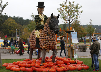 Visitors look at a dressage rider made of pumpkins at the pumkin festival in Klaistow
