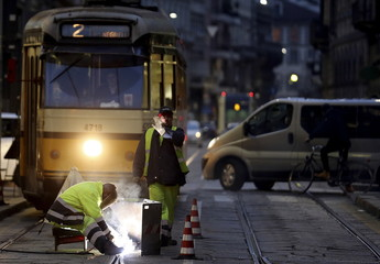 A worker welds a tram track in downtown Milan